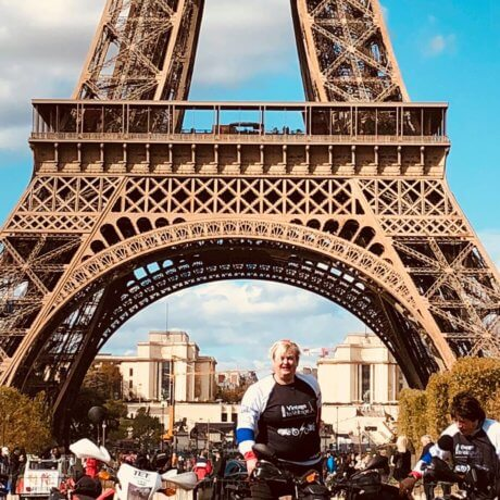 a photo of people on motorbikes in front of the Eiffel Tower
